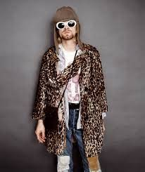 Photo of Kurt Cobain wearing sun glasses, a beaver hat, jean,s and a cheetah print coat with a scarf